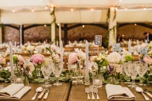Long tables dressed for wedding breakfast with floral displays and cutlery: wedding marquee hire
